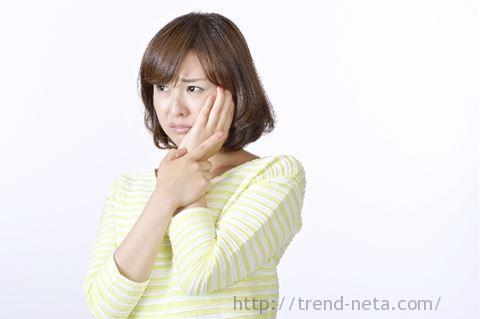 口の痛みを押さえる女性
