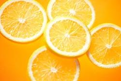 オレンジ色の背景のカットしたレモン