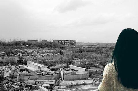 地震の廃墟を見つめる女性