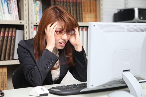 パソコンを前に困った女性